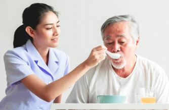 lady caregiver feeding the old man