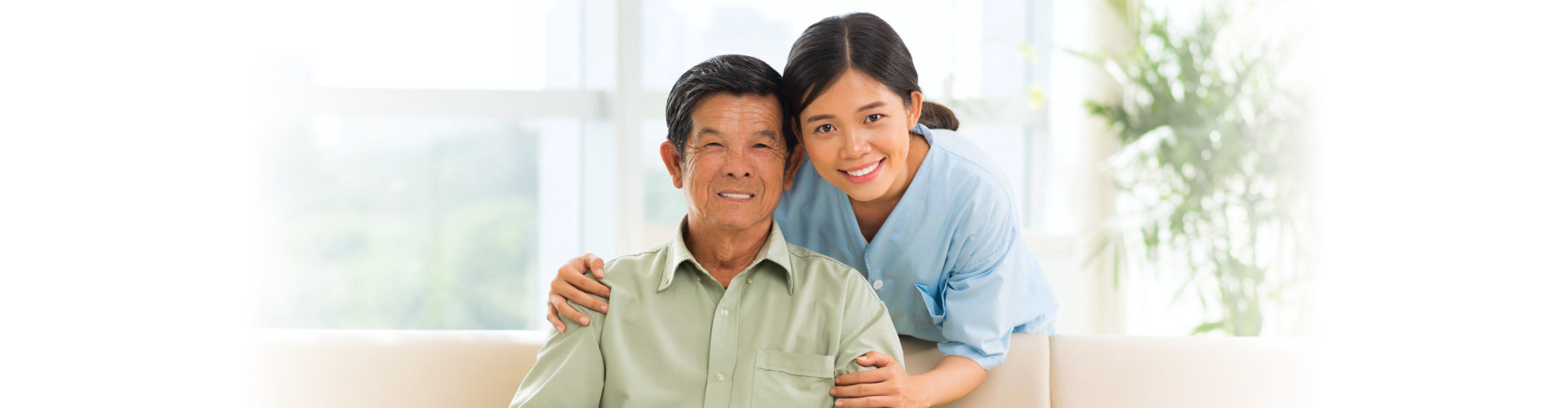 lady caregiver with senior man smiling