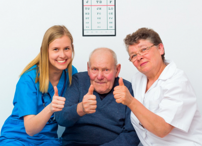 elderly man showing thumbs up with his caregivers