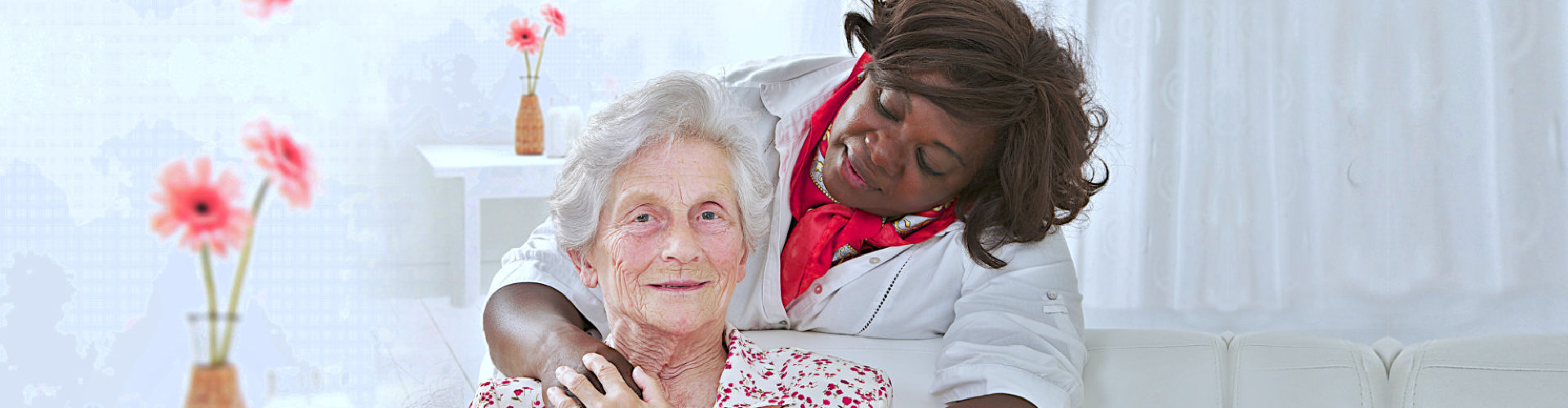 elderly woman smiling with her caregiver watching
